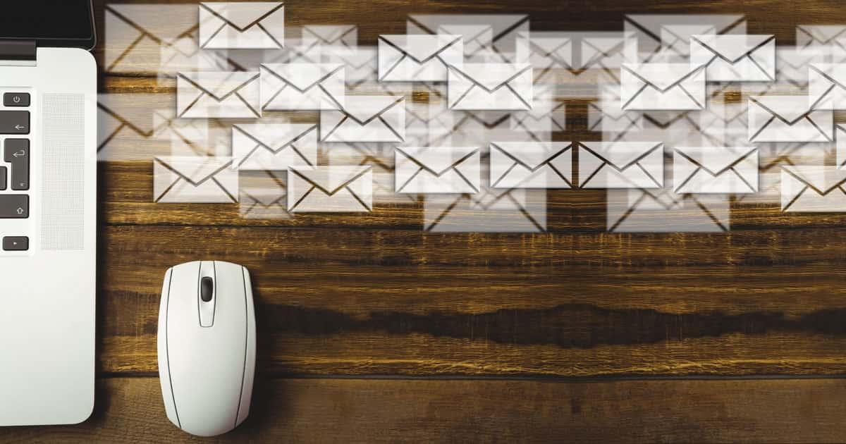 armada d'enveloppes quittant un ordinateur portable posé sur un bureau de bois sombre vu de dessus