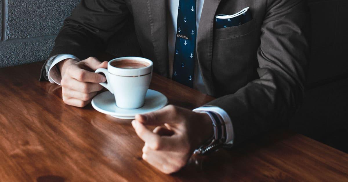 homme en veste et cravate avec pochette assortie buvant un café
