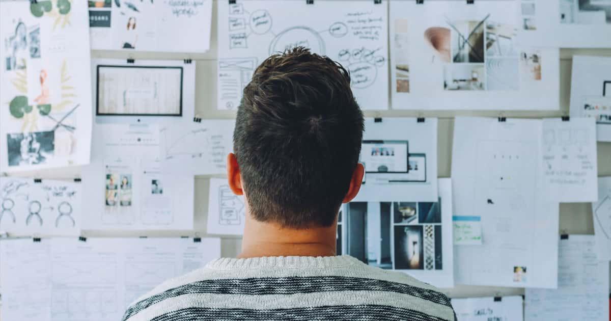 homme de dos contemplant un mur couvert de notes