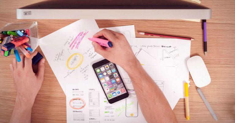 vue plongeante sur une main tenant un marqueur rose sur un bureau couvert de notes et de stylos devant un écran de mac