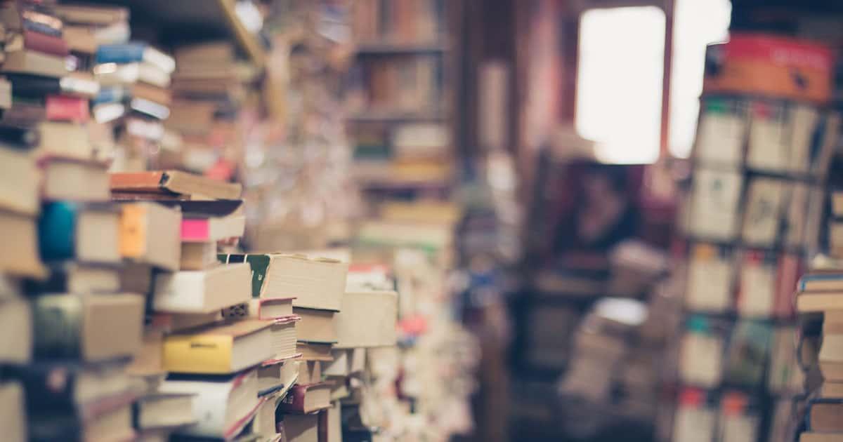 pile de livres jusqu'au plafond devant une fenêtre au fond