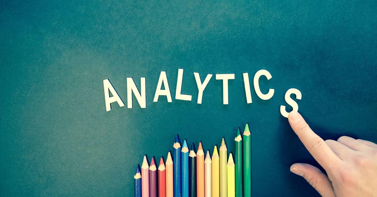 lettres issues d'un jeu pour enfants écrivant le mot analytics. Le S final est en cours de placement par une main. Des crayons de couleurs sont disposés en forme de graphique sous la composition