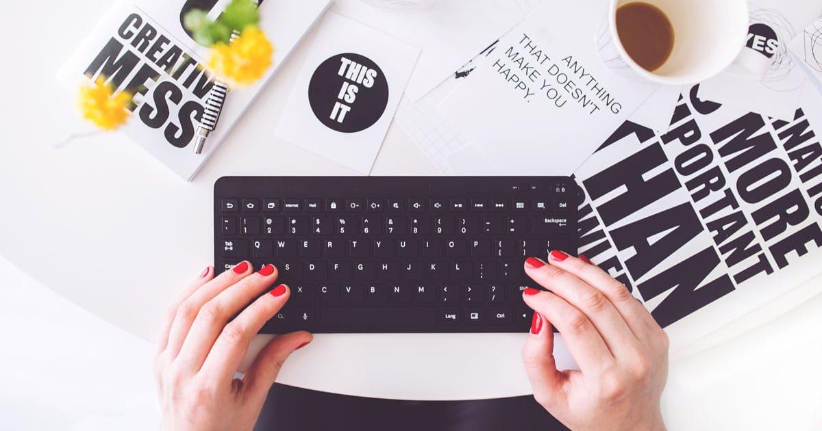 mains aux ongles vernis prêtes à taper sur un clavier sur un bureau couvert de papiers
