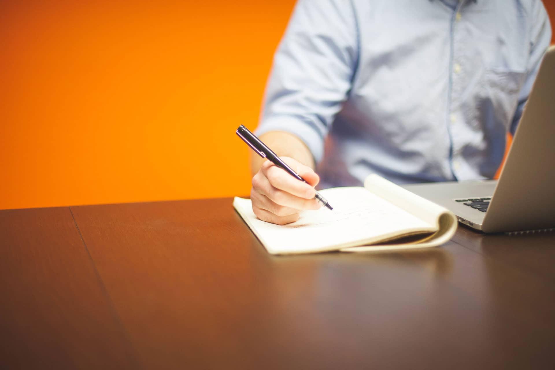 homme écrivant sur un cahier dans un bureau au mur orange